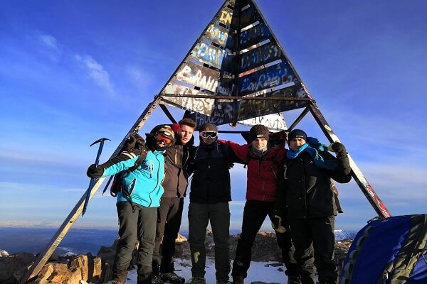 group of people at the peak of mount toubkal