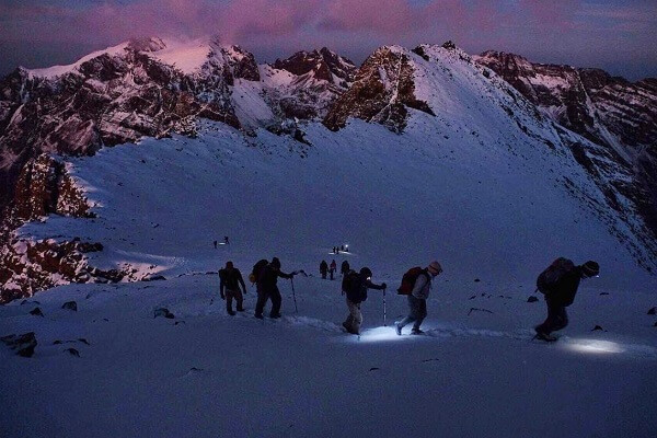 people climbing a mountain in early morning