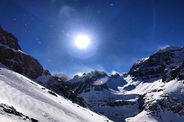 mountain covredwith snow and sun shines