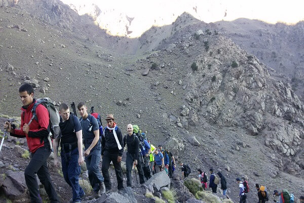 group of people walking in the mountains