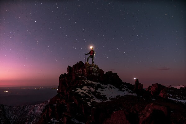 man standing on rock with head lamp