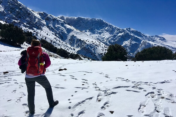 man standing in mountain passe with snow on