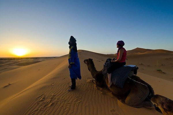 setting on camel looking at sunset