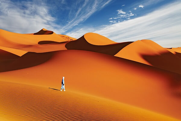 a solo man in midle of sund dunes in morocco