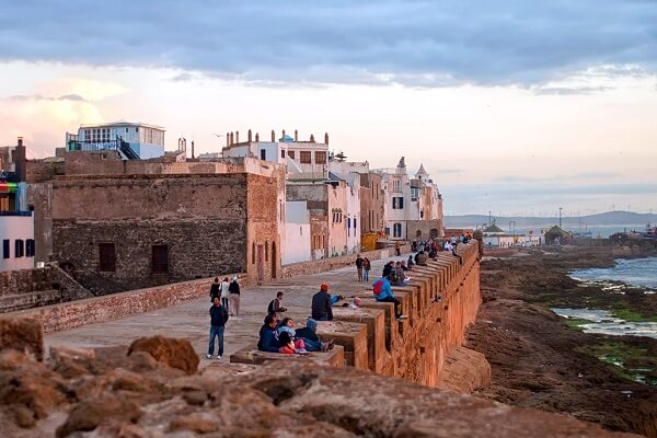 people siting on a wall near the sea