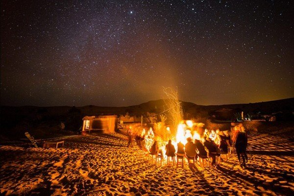 people siting around fire under the stars of desert
