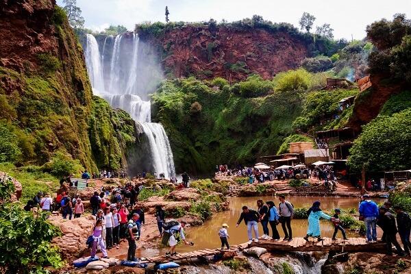 people crossing a bridge front of waterfalls