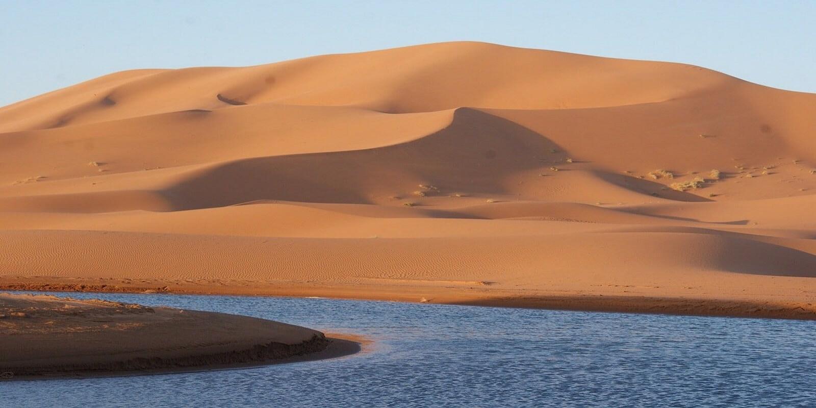 sand dunes and lake in sahara desert
